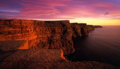 An orange and pink sunset bathes the Cliffs of Moher