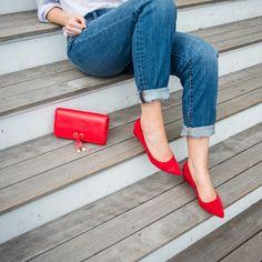 Boyfriend jeans, a classic button up, and red accessories are the staples for effortless style.