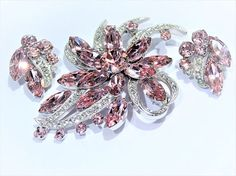Item # 121631  An amazing designer signed EISENBERG ICE,circa 1950s, pink and crystal rhinestone brooch and matching clip on earrings demi parure set. According to American Costume Jewelry by the Brunialtis, the Eisenberg Ice in all capital block letters was used from 1949-1958.  Brooch consists of a stunning pink round surrounded by 6 pink navettes to form the top layer. Underneath are 6 more pink navettes and 7 smaller pink rounds, with pave crystal rhinestones set throughout. All pink…