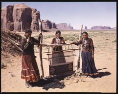 Navajo women stand near their loom with their woven Navajo indian rug. Native American craft in Monument Valley, Utah