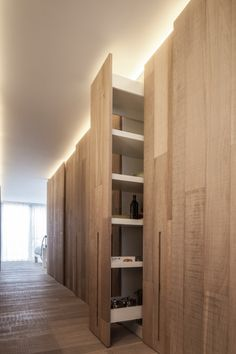 A smart idea of pull out shelving as a space organizer hidden behind a wall