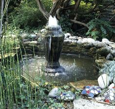 Large basin fountain in the middle of a backyard pond surrounded by rocks
