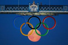 On August 3rd, 2012 a full moon graced the London skies. Reuters photographer Luke MacGregor took this incredible shot of the moon rising through the Olympic Rings hanging beneath the Tower Bridge