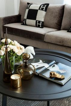 Chic living room features a mink brown velvet sofa adorned with black and white Hermes pillows facing a round black coffee table topped with a Kelly Wearstler Brass Foot Paper Weight.