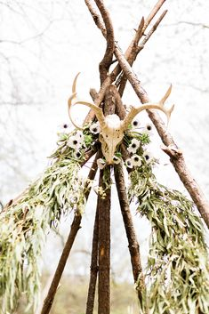 Naked branch tipi with animal skull ceremony backdrop · Rock n Roll Bride