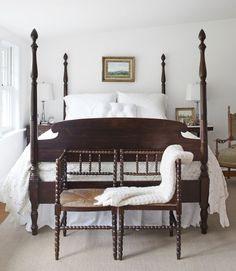 farmhouse white with beautiful mahogany four poster bed, simple artwork, and a pair of antique 1920's english oak corner chairs.  crisp, and classic.