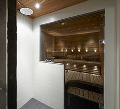 Savunharmaa lasiseinä saunan ja kylpyhuoneen välillä.