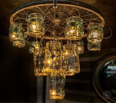 A chandelier made out of a bike wheel, fishing hooks and mason jars!