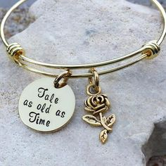 OUR STORY: At KK&Whimsy, we love incorporating personalized elements into our style! We know that each of our clients have a unique story and have walked a unique journey that ultimately created who they are at their core. Our hand stamped jewelry is a tribute to your life, your family and all the things you love. ITEM DESCRIPTION: This gold Beauty and the Beast inspired bangle is made of a 3/4, 20 gauge nickel disc and is hand stamped with the phrase Tale as old as Time. It is coupled with…