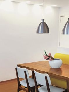 Na área de refeições, um sofá amarelo de couro sintético é o destaque da decoração. Uma mesa de cadeira maciça é servida por cadeiras, que acrescentar branco à combinação quente. Sofá amarelo de couro sintético. Com 1,60 x 0,60 x 0,95m. Art & Pani, R$ 1440 (com revestimento).