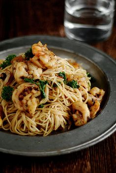 200 grams angel hair pasta  50 grams butter  1 tablespoon olive oil  5 cloves garlic, sliced  2 teaspoons dried chilli flakes  1 tablespoon shredded lemon zest  12 (raw) prawns (shrimp), peeled, cleaned and halved lengthways  1 tablespoon lemon juice  ¼ cup flat-leaf parsley leaves, roughly torn  sea salt and cracked black pepper to taste