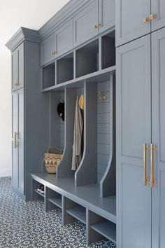 Well appointed blue mudroom boasts white and blue cement floor tiles accenting a blue bench fitted with shoe shelves and positioned against a blue shiplap trim finishing open lockers accented with brass hooks. lockers with bench Mudroom Cubbies, Mudroom Cabinets, Mudroom Laundry Room, Laundry Room Design, Mud Room Lockers, Shoe Storage Mudroom, Entryway Storage, Armoire Entree, Shiplap Trim
