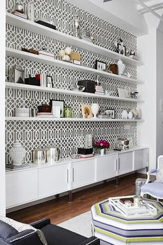 low cabinet and shelves with background pattern paper -- Kelly Wearstler imperial trellis charcoal wallpaper, White floating shelves, white Ikea Torsby media cabinets, white carthage pierced lanterns, octagon striped blue white green purple ottoman, charcoal gray nailhead trim wingback chairs and purple French chair! I could drink water and be a little dizzy with the wallpaper...still love it...