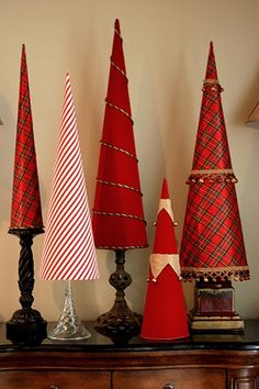 Use old candle holders or tall glasses (or buy some from charity shops) as bases and add stiffened fabric or wrapping paper cones for a delightful Christmas arrangement.