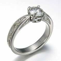 Engagement Ring 6-12: Round cut diamond prong set in platinum with vine detailing on the sides