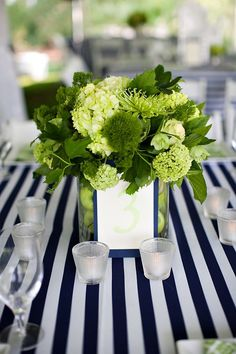 Navy blue and white stripes tablecloth with green floral centerpieces, great for a Seahawks theme
