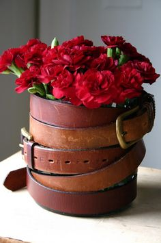 Los cinturones sirven para decorar latas que funcionan como masetas.