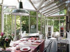 Salle à manger aménagée dans une véranda, donnant l'impression de prendre ses repas en pleine nature