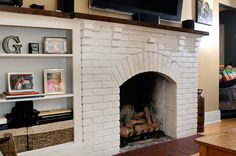 Painted brick fireplace with built-in shelving in living room