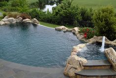 Vanishing edge pool and spa  The faux stone and vanishing edge design of this pool (also known as an infinity pool) impart the natural look of a pond, blending with the surroundings.