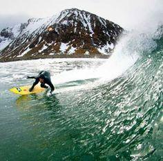 Image: Dane Gudauskas surfs off the Lofoten Islands in the Arctic region of Norway (© Chris Burkard/Caters News)