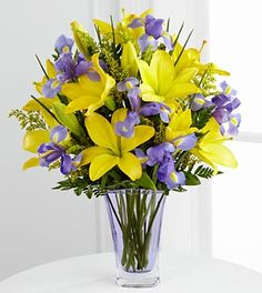 The FTD® Touch of Spring® Bouquet is a sunny display of Spring's majestic beauty. Brilliantly bright yellow Asiatic lilies mingle with purple iris and gorgeous greens arranged in a designer pale lavender glass vase. It's a cheerful expression of Spring's sweetness.
