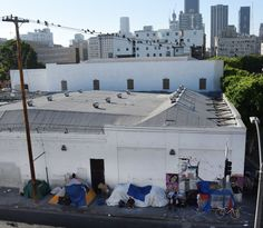 Los Angeles homelessness emergency: 'A city of shanties' James Cook, BBC News, 7 October 2015) Shown: People ride bicycles past tents on Skid Row with the financial district of Los Angles, California, in the background, September 23, 2015