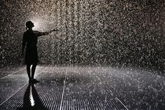 A woman extends her arm out while walking through the Rain Room, an interactive art installation at The Curve inside London's Barbican Centre. Despite the torrential downpour in this 100-square-meter room, visitors remain dry thanks to 3D sensory cameras that detect the position of each individual and stops the rain overhead...Awesome!!