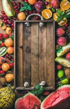 #Summer fresh fruit variety  Summer fresh fruit variety with rustic wooden tray in center top view copy space vertical