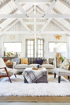 barn conversion with white walls and ceiling. Sheepskin rug.