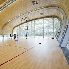 A steel shell curls over the arched frame of this sports hall near Sydney.