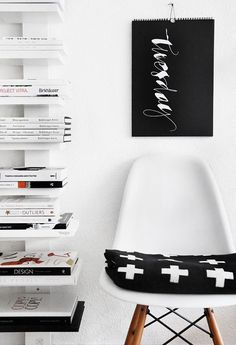 Eames chair. Black and white cross blanket. Shelf.