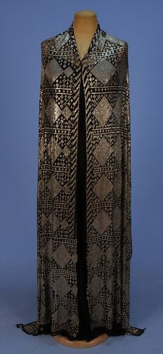 EGYPTIAN ASUITE SHAWL, 1920's. Black cotton net heavily decorated allover with hammered silver in a pattern of diamond bands