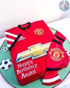A simple Manchester United shirt cake with fans scarf in home colours for die hard ManU fan. Base decorated with edible footballs for the added feel. Come on Red Devils Rep your colours Football Cakes For Boys, Football Birthday Cake, Dad Birthday, Birthday Cakes, Happy Birthday, Manchester United Birthday Cake, Manchester United Shirt, Soccer Cake, Shirt Cake