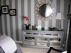 Old dresser with mirrored drawers, updated with hardware and metalic paint.  Mirror above surrounded by leave petals made from sea shells.