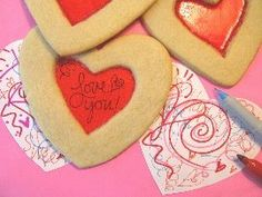 """Secret Message Cookies - """"Cookies with a twist! Red candy melted in the center of each cookie acts as a decoder on your handwritten valentines. On white paper simply write your secret message with a light-blue fine point marker. Then, using orange, red, and pink markers, doodle shapes, scribbles, or words over the rest of the paper. Go ahead and doodle right over your secret message because your decoder cookie will only reveal your secret message and everything else will disappear!"""""""