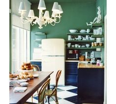 This kitchen boasts an unusual color palette with deep green walls and dark blue cabinetry. The floor follows the lead of these colors and is painted a deep blue along with a bright white. Add the large white chandelier and vintage style refrigerator and this becomes a space full of unique style. ~ painted floors wood flooring