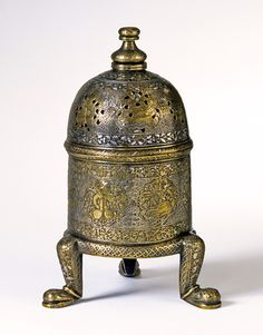 Incense burner, cast brass, engraved and inlaid with silver and gold Northwestern Iran; 1st half of 14th century  Cylindrical incense burners on three legs and with a domed lid were common from Iraq to Egypt in the 13th and 14th century, but are also known from Iran under the Il-Khanids. All had a horizontal handle and contained a tray for charcoal, both of which are usually missing.
