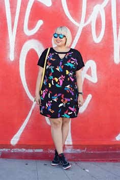 Spring Outfits 2015: 50 Flawless Looks to Copy Now - colorful abstract printed shift dress worn with mirrored sunglasses, and yellow bag, and sneakers.
