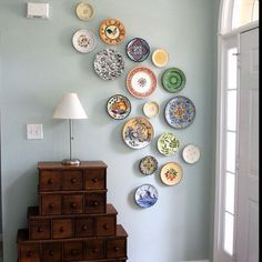 Colorful plates as wall decoration. I love the asymmetric swirl movement of the placement of these plates.