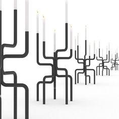 Een speels buizenstelsel volledig omgebogen tot een vijfarmige kandelaar, door Frederik Roijé. De creatieve designer ontwerpt iedereen uniek product met nieuwsgierigheid, schoonheid en liefde voor verrassingen. Uitgevoerd in wit en donker grijs.