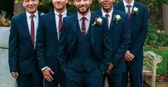 Groomsmen in three piece navy suits with maroon ties - Image by Hannah May - Autumnal rustic themed wedding with Navy, Maroon & Gold Colour Scheme. Bride in Lace Wedding Dress & Bridesmaids in beaded Navy dresses. Groom wears a suit from Next & patterned