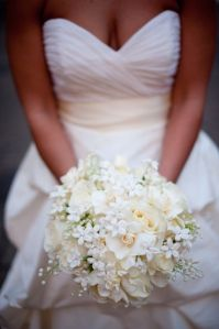 Stephanotis and Lily of the Valley, were combined with white Akito Roses and Gardenias. The stems of the bouquet were wrapped in silk organd...