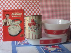 A still-life of vintage kitchen items: Sunbeam electric mixer manual, decorated sifter, plus a white and red bowl with a matching baking dish.