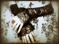 Your wrist rolls. You pull every finger into a slow fist then release it, arching your hand in appeal. The black lace, the delicacy of your
