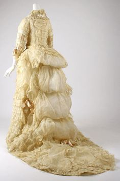 Late Victorian cotton ivory wedding dress: puffed, pleated, tucked, laced, bowed, draped & bustled (circa 1870s)  Over-the-top, but an amazing example of costume artistry.