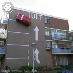 Car On The Wall - Strange Parking Place;  art by Theo van Laar;  during the night, the car's headlights are switched on;  located in The Hague, Netherlands