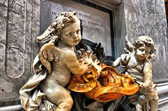 Cherubs hold a bright orange holy water font at the base of the stature of St. Peter of Alcantara near the entrance of St Peter's Basilica in this HDR image. While thse little cherubs seem small, they are actually 2 meters high.