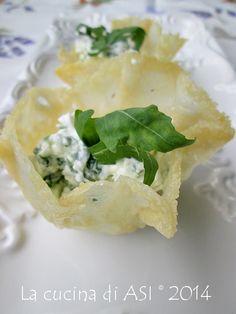 Semplici cestini di parmigiano farciti con una crema saporita di crescenza e rucola decisamente invianti! Ricetta antipasto La cucina di ASI