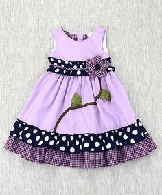 Trimmed with fluttery ruffles and punctuated by a bold floral accent, this classic cotton frock invites leaps and twirls with an adorable A-line profile.